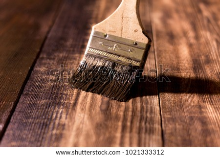 male hand paint wooden surface with brown paint using a paintbrush #1021333312