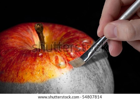 Male hand painting a fresh red wet apple which is partly black and white and partly colored