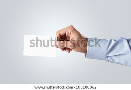 Male hand passing blank business card with copy space