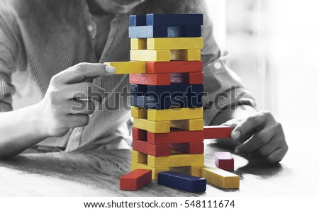 Male hand placed on a tower of wooden blocks on the table concept and strategic planning. #548111674