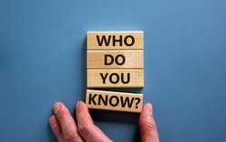 Male hand placing a block with word 'know' on a blocks tower with words 'who do you know'. Beautiful blue background. Business concept. Copy space.