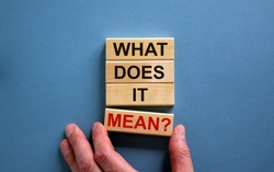 Male hand placing a block with word 'mean' on a blocks tower with words 'what does it mean'. Beautiful blue background. Business concept. Copy space.