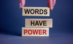 Male hand placing a block with word 'words' on top of a blocks tower with words 'words have power'. Beautiful grey background. Copy space. Business concept.
