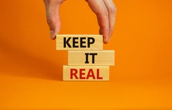 Male hand placing a blocks with word 'keep' on top of a blocks tower with words 'keep it real'. Beautiful orange background. Copy space. Business concept.
