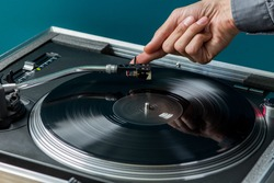 Male Hand Placing Stylus on Vinyl Record