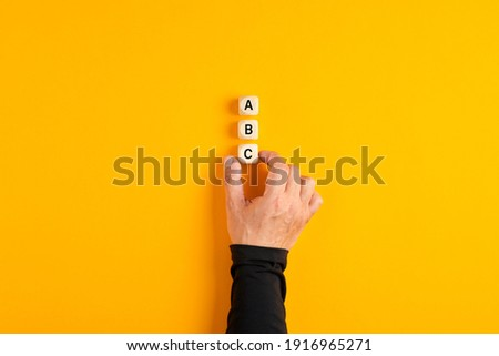 Male hand placing three wooden blocks with the letters of a b and c on yellow background. Business plan decision, choice of alternatives. Stock fotó ©