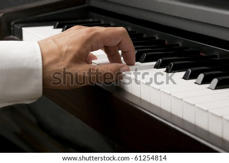 Male hand playing on a piano - stock photo