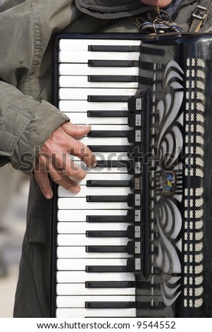 male hand playing on accordion