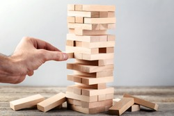Male hand playing wooden blocks tower game on grey background