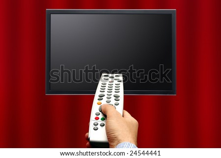 male hand pointing a remote control to a screen in front of a curtain background