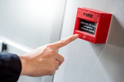 Male hand pointing at red fire alarm switch on concrete wall in office building. Industrial fire warning system equipment for emergency.