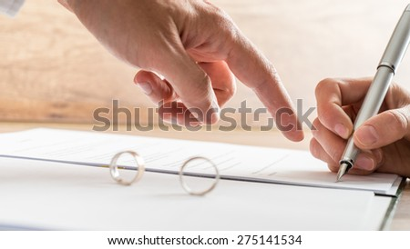 Male hand pointing to a divorce paper on which a woman is busy writing with a pen in a close up conceptual view.