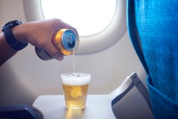Male hand pouring beer into a plastic glass and making too much foam head on the airplane. Happy man drinking beer on airplane.