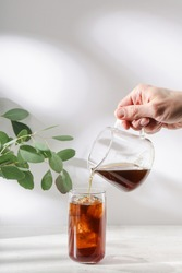 Male hand pours coffee into a glass full of ice cubes. Cold refreshing summer drink or fruit lemonade cocktail preparation. White table. Eucalyptus in vase decoration. Sunlight rays. Copy space.