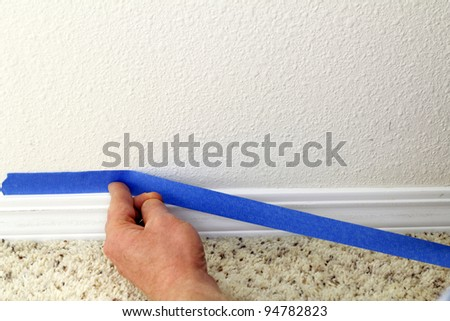 Male hand preparing to paint wall trim by placing blue painter's tape on the wall above it for protection.