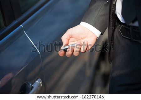 Male hand presses on the remote control car alarm systems