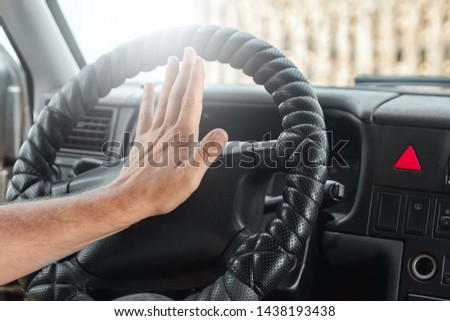 Male hand presses the signal on the steering wheel of the car. Close-up. Emergency, accident, traffic violation.