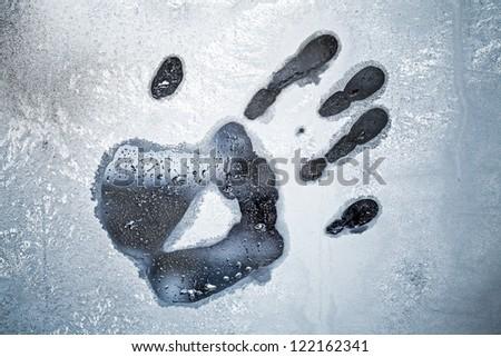 Male hand print on frozen windows glass