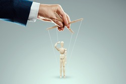 Male hand, puppeteer controls puppet, doll salutes, soldier. The concept of the army, orders, manipulation, control army