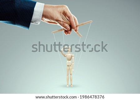Male hand, puppeteer controls puppet, doll salutes, soldier. The concept of the army, orders, manipulation, control army Foto stock ©