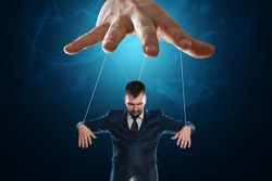 Male hand, puppeteer controls the puppet puppet with strings. A doll on her knees. The concept of world conspiracy, world government, manipulation, control