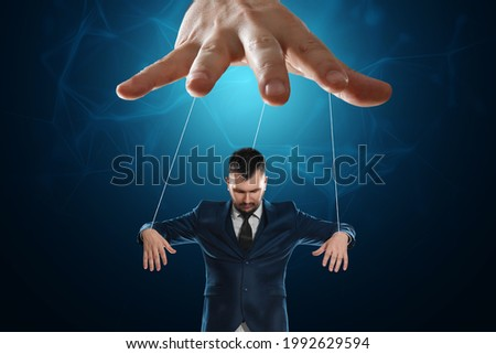 Male hand, puppeteer controls the puppet puppet with strings. A doll on her knees. The concept of world conspiracy, world government, manipulation, control Foto stock ©