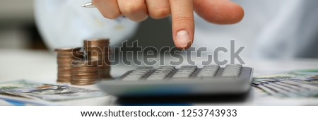 Male hand push key silver calculator is lying on desk cash dollar plots in home office setting. Calculation of family expenses social income population freelance irs situation growth research concept #1253743933