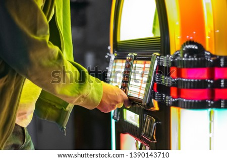 Male hand pushing buttons to play song on old Jukebox, selecting records #1390143710