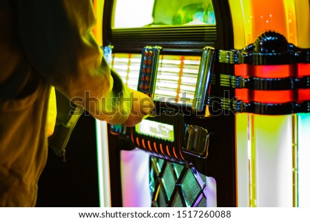 Male hand pushing buttons to play song on old Jukebox, selecting records #1517260088
