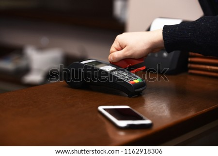 Male hand puts bankcard into reader on defocused background. Credit card terminal for cashless payments near mobile phone. Electronic finance and shopping concept. Payment with credit card.