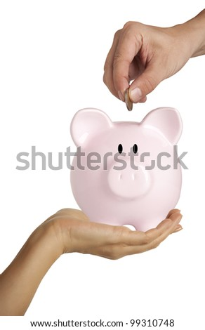 Male hand putting coin into a piggy bank isolated on white