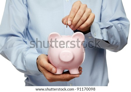 Male hand putting coin into a piggy bank isolated on white background