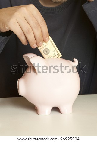 Male hand putting dollars into a piggy bank