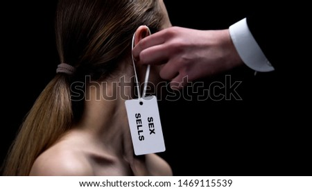 Male hand putting sex sells tag on female ear, sexual slavery, human rights