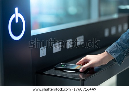 Male hand putting smartphone on wireless charger or induction charger. Mobile phone power charging service station in public area.