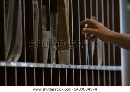 Male hand reaching for sorted post or mail in pigeon holes in a postal depot in a corporate business #1439034374
