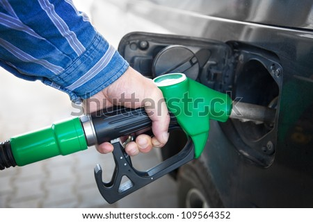 Male Hand Refilling the black Car with Fuel on a Filling Station