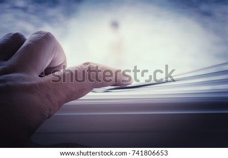 male hand separating slats of venetian blinds with a finger to see through