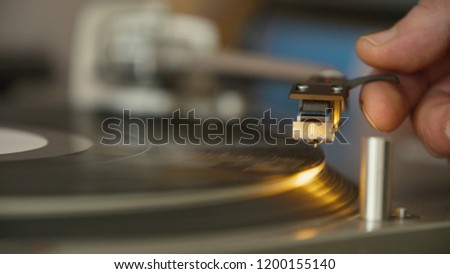 Male Hand Sets The Audio Needle To Play On A Black Vinyl Record On A Record Player. #1200155140