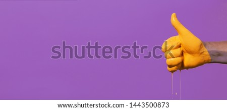 """male hand showing sign thumb up with paint flowing down on a colored background. creative idea, creative concept, gesture """"class"""" #1443500873"""