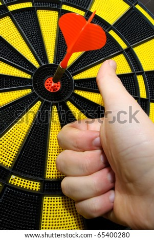 Male hand showing thumbs up with bulls eye on dart game board