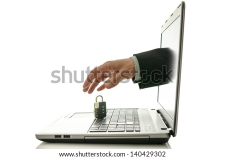 Male hand stealing padlock through laptop monitor. Concept of internet theft.