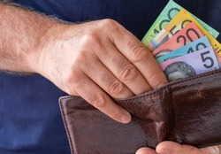 Male hand taking Australian bank notes from a worn brown wallet.  Financial