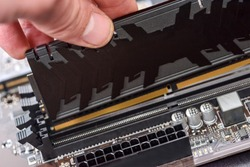 Male hand taking out ram memory on motherboard