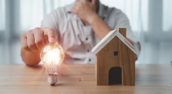 male hand touching a light bulb with house model on desk. The concept of installment and reduction of home loan interest, saving energy and money concept. idea for Buying a house.