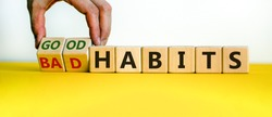 Male hand turning cubes and changes the expression 'bad habits' to 'good habits'. Beautiful yellow table, white background. Concept. Copy space.