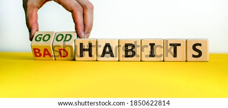 Male hand turning cubes and changes the expression 'bad habits' to 'good habits'. Beautiful yellow table, white background. Concept. Copy space. Stockfoto ©