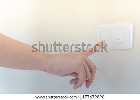 Male hand turning off the light when leaving. Pressing index finger on lighting switch panel control. Energy saving and environmental conservation concepts #1177679890
