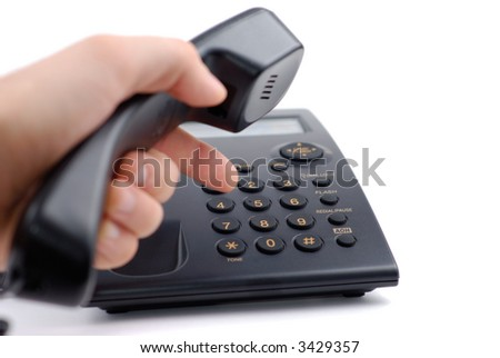 Male hand typing phone number on black telephone isolated over white bacground