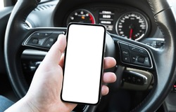 Male hand using smartphone in car. Man driving a car. Smartphone in a car use for Navigate or GPS. Mobile phone with isolated white screen. Blank empty screen. copy space. Empty space for text.